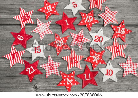 Advent calendar with stars on old wooden background - stock photo
