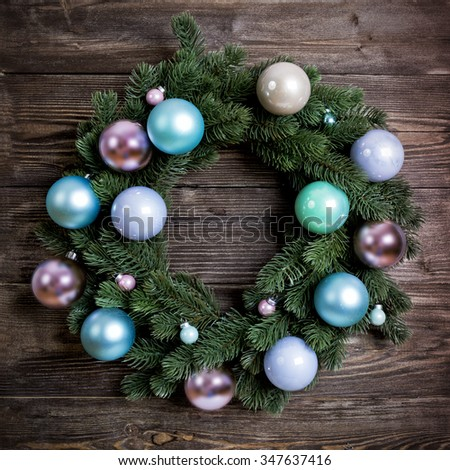 Advent Christmas wreath with pink and blue baubles on wooden door decoration - stock photo