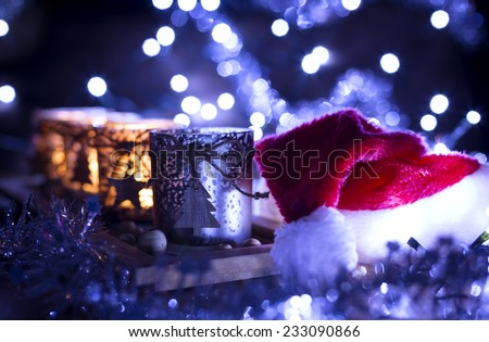 Advent, four candles Christmas decoration and next Santa Claus hat on a background of lights - stock photo