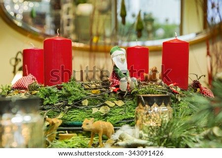 Advent wreath ensemble with with four red candles,cute forest scene and handmade cloth Santa Claus. - stock photo