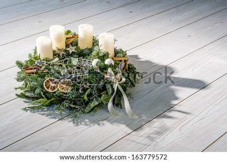 Advent wreath of twigs with white candles and various ornaments - stock photo