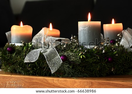 Advent wreath with burning candles on an oak table - stock photo