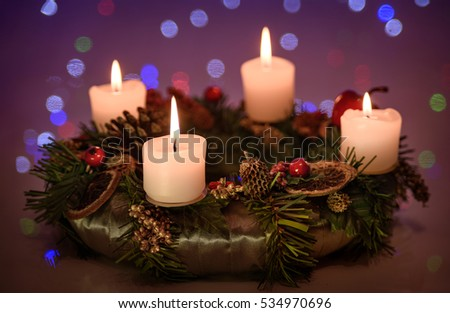 Advent wreath with four burning candles over a soft focus Christmas light background