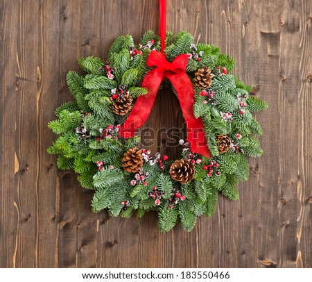 Advent wreath with red ribbon over wooden wall