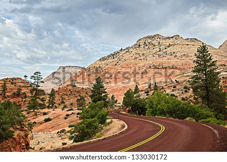 Adventure At Desert Mountain Formations In Zion National Park, Curved Red Rock Asphalt Road Running Through The Landscape Of Sandstone Backpack Country In Utah, USA