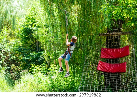 Adventure climbing high wire park - little boy on course in mountain helmet and safety equipment - stock photo