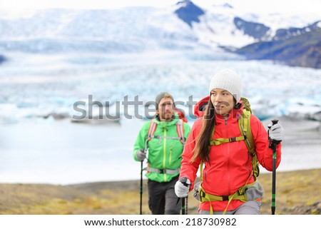 Adventure hiking people by glacier on Iceland walking with hiking poles by glacial lagoon / lake of Fjallsarlon, Vatna glacier, Vatnajokull National Park. Couple visiting Icelandic nature. - stock photo