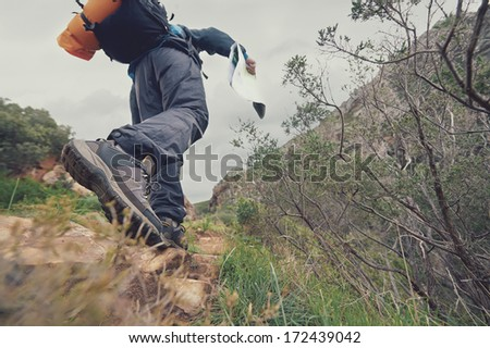 Adventure man with map in wilderness - stock photo