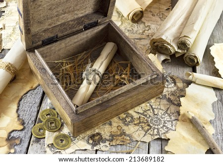 Adventure still life with maps and scrolls on wooden background - stock photo