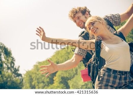Adventure, tourism, enjoying summer time together - young couple tourists hikers having fun open arms outdoor