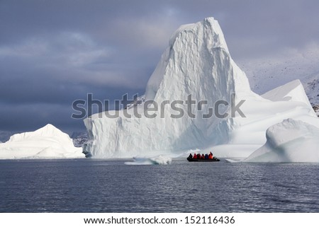 Adventure tourists and Iceberg in Scoresbysund in eastern Greenland - stock photo