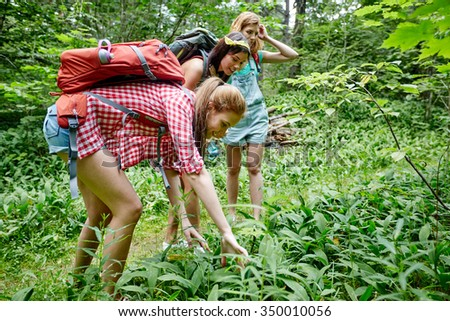 adventure, travel, tourism, hike and people concept - group of smiling friends with backpacks looking for berries in grass in woods - stock photo