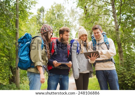 adventure, travel, tourism, hike and people concept - group of smiling friends with backpacks and tablet pc computers outdoors - stock photo