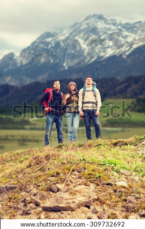 adventure, travel, tourism, hike and people concept - group of smiling friends with backpacks over mountains background