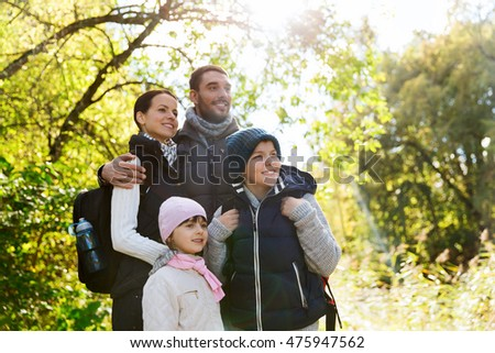 adventure, travel, tourism, hike and people concept - happy family walking with backpacks in woods