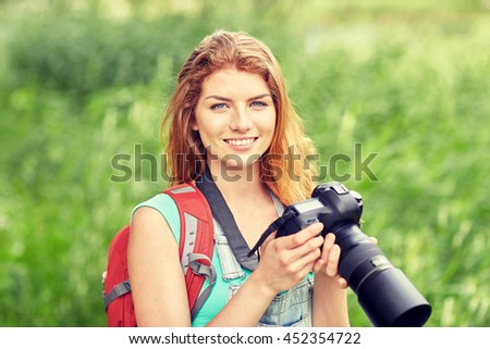 adventure, travel, tourism, hike and people concept - happy young woman with backpack and camera photographing outdoors - stock photo