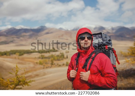 Adventure, travel, tourism, hike and people concept - man with backpack in mountain - stock photo