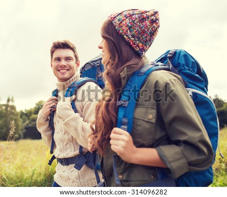 adventure, travel, tourism, hike and people concept - smiling couple walking with backpacks outdoors - stock photo