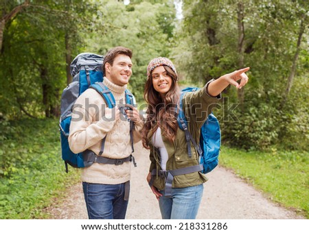 adventure, travel, tourism, hike and people concept - smiling couple with backpacks outdoors - stock photo