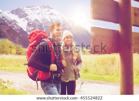 adventure, travel, tourism, hike and people concept - smiling couple with backpacks standing at signpost over alpine mountains and hills background - stock photo