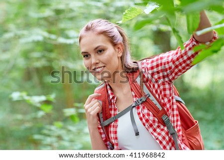 adventure, travel, tourism, hike and people concept - smiling young woman with backpack hiking in woods - stock photo
