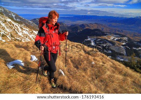 Adventure travel with backpacker woman walking a mountain slope