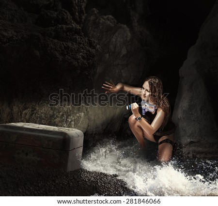Adventure. Woman traveler and explorer in sea cave, shining a flashlight into the chest searching treasures