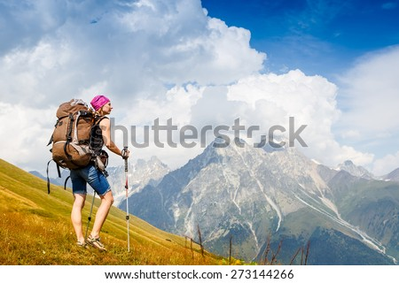 Adventure woman with backpack enjoy the view in the mountains - stock photo