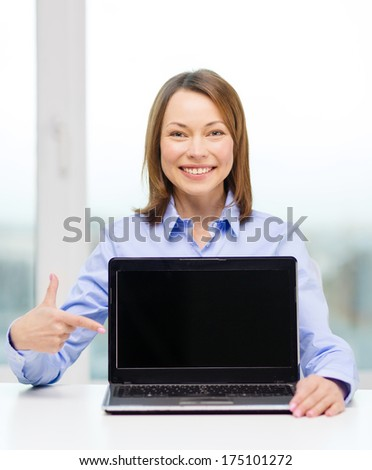 advertisement, business and technology concept - smiling businesswoman pointing finger to blank black laptop screen - stock photo