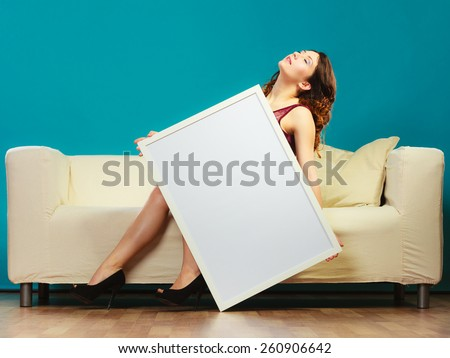 Advertisement concept. Elegant young woman sitting on sofa holding blank presentation board. Girl showing banner sign billboard copy space for text.