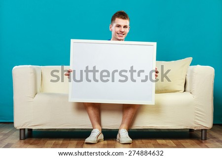 Advertisement concept. Young man sitting on sofa with blank presentation board. Male model showing banner sign billboard copy space for text on blue - stock photo