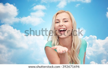 advertisement, emotions and people concept - smiling young woman or teenage girl holding something on hand over blue sky and clouds background - stock photo