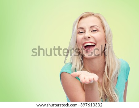 advertisement, emotions and people concept - smiling young woman or teenage girl holding something on hand over green natural background - stock photo