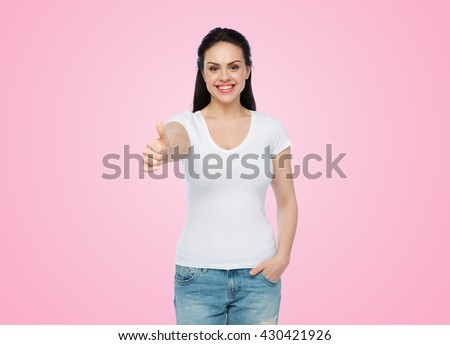 advertisement, gesture, clothing and people concept - happy smiling young woman or teenage girl in white t-shirt showing thumbs up over pink background - stock photo