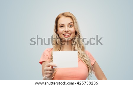 advertisement, invitation, message and people concept - smiling young woman or teenage girl with blank white paper card over gray background - stock photo