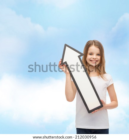 advertising and child concept - smiling little girl with blank arrow pointing up