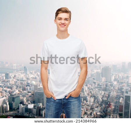 advertising and people concept - smiling young man in blank white t-shirt over city background - stock photo