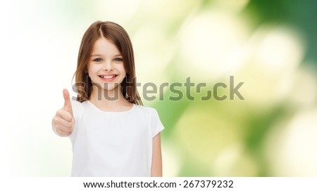 advertising, childhood, ecology and people - smiling little girl in white blank t-shirt showing thumbs up gesture over green background - stock photo
