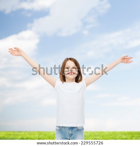 advertising, childhood, gesture and people concept - smiling little girl in white t-shirt with stretched out arms over natural background - stock photo