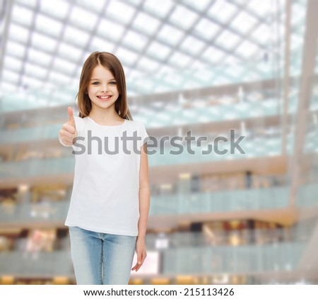 advertising, childhood, gesture, consumerism and people - smiling girl in white t-shirt showing thumbs up over shopping center background - stock photo