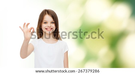 advertising, childhood, gesture, ecology and people - smiling little girl in white blank t-shirt showing ok sign over green background - stock photo