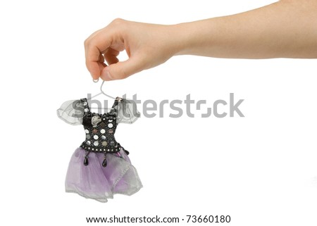 Advertising clothing. Hand holds the dress for a doll on a white background. - stock photo