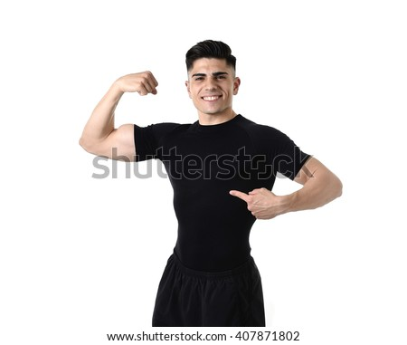 advertising corporate portrait of young attractive sport man with big strong body pointing with his finger on his black t-shirt with copy space for adding gym and fitness health club logo  - stock photo