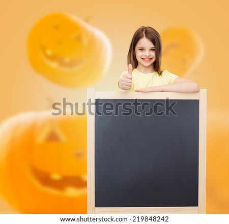 advertising, gesture, education, holidays and people concept - smiling little girl with blackboard showing thumbs up over halloween pumpkins background - stock photo