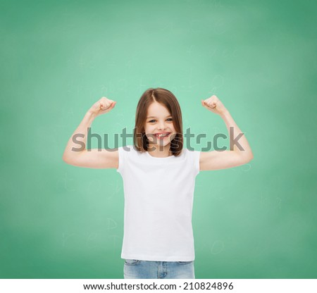 advertising, gesture, school, education and people - smiling little girl in white blank t-shirt with raised arms over green board background - stock photo