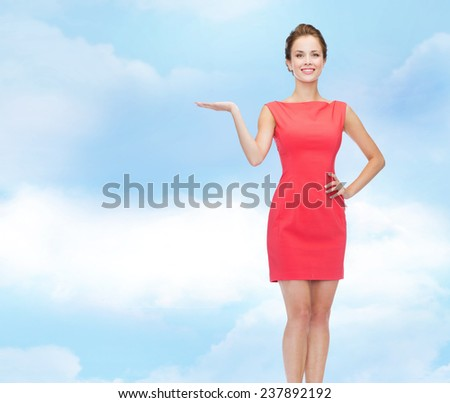 advertising, holidays and people concept - smiling young woman in red dress holding something on palm of her hand over blue cloudy sky background - stock photo