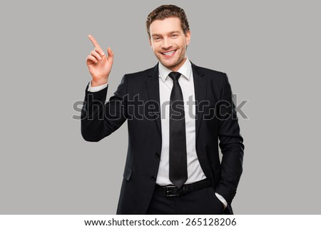 Advertising your product. Confident young man in formalwear looking at camera and smiling while pointing away and standing against grey background - stock photo