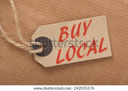 Advice to Buy Local printed on a brown paper price tag as a means of supporting local suppliers and producers - stock photo