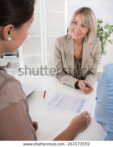 Adviser, broker and customers sitting at desk in the office. Young couple planning their retirement arrangements. - stock photo
