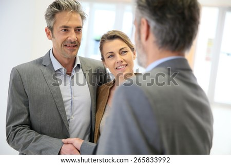 Adviser giving handshake to clients  - stock photo